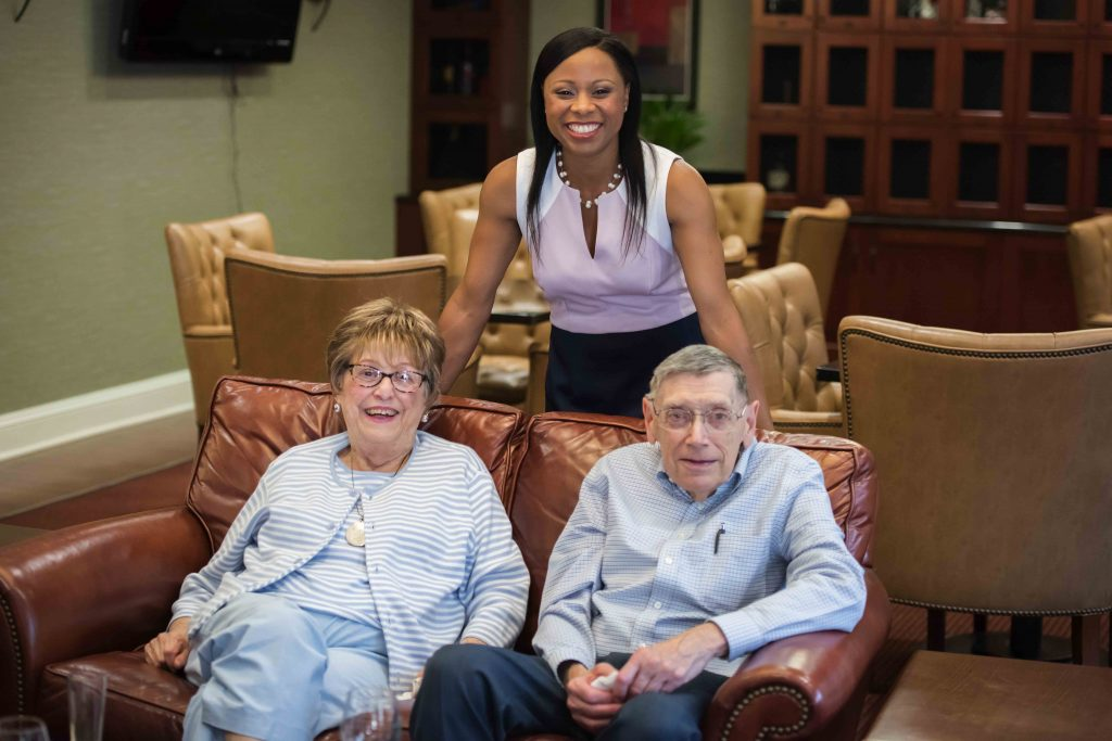 Nicole Smith, Director of Community Programming, poses with residents in the Cherry Blossom Lounge.